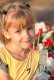 Little girl smiling  and the flowers Stock Images