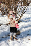 Little girl smiling with hands in pockets in snow Royalty Free Stock Photos