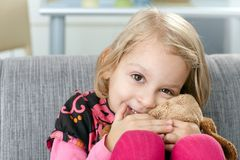 Little girl smiling impishly on sofa Royalty Free Stock Images