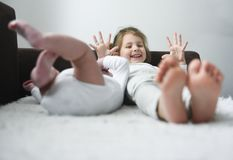 Little girl is smiling laying with her baby brother royalty free stock images