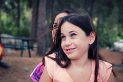 Little girl smiling and looking away while sitting on her mother Royalty Free Stock Image