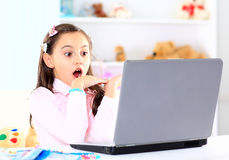 little girl smiling and looking at laptop Stock Photo