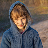 Little girl smiling looks at camera while a walk in the autumn p Royalty Free Stock Image