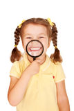 Little girl smiling through magnifying glass. Stock Images