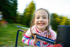Little girl smiling on a moving merry-go-round Royalty Free Stock Images