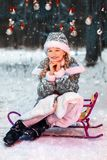 Little girl smiling in the new year forest on a sled. Snow Maiden in a festive costume. winter, snow is falling. toys on the tree stock photos
