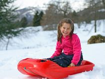 Little girl smiling over bob on snowy mountain Stock Images