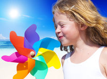Little Girl Smiling Playing with Wind Toy. Little Girl Smiling Playing with Her Wind Toy by the Beach Stock Photography