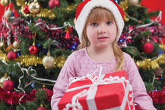 Little girl smiling with present near the Christmas tree Royalty Free Stock Photo