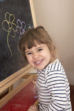 Little girl smiling proud of her drawing of flowers on blackboard royalty free stock image