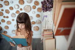 Little girl smiling and reading book; Royalty Free Stock Images