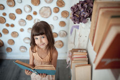 Little girl smiling and reading book; royalty free stock photos