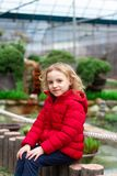 Little girl smiling in a red jacket in nature royalty free stock photos