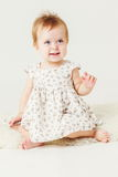Little girl smiling. Little girl sitting on the sheep's clothing Royalty Free Stock Photos