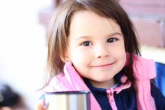 Little girl smiling sitting at the table outdoors. Eating, restaurant, lunch, beautiful, summer, happy, healthy, child, cafe, small, kid, cute, young, people stock images