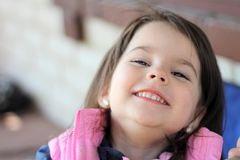Little girl smiling sitting at the table outdoors. Eating, restaurant, lunch, beautiful, summer, happy, healthy, child, cafe, small, kid, cute, young, people stock photos