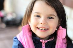 Little girl smiling sitting at the table outdoors. Eating, restaurant, lunch, beautiful, summer, happy, healthy, child, cafe, small, kid, cute, young, people stock photo