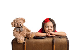 Little Girl smiling with suitcase and toy bear Stock Photo