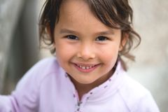 Little girl smilling at camera. Isolated over grey in studio royalty free stock photo