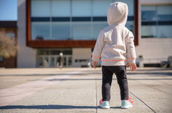 Little girl with sneakers and hoodie standing Stock Photos