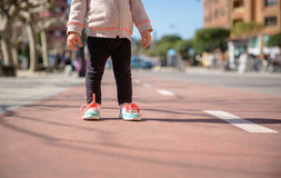 Little girl with sneakers and leggins standing Stock Photos