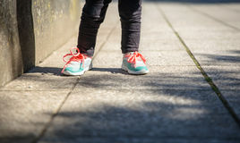 Little girl with sneakers and leggins training outdoors. Closeup of little girl legs with sneakers and black leggins training outdoors Stock Photos