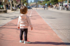 Little girl with sneakers standing over a city Stock Photos