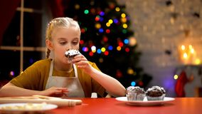Little girl sniffing chocolate muffin, cozy Christmas mood, holiday atmosphere. Stock photo royalty free stock image