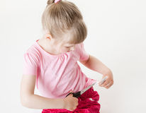 Little girl snipping off a brand label. White background Royalty Free Stock Images