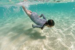 Little girl snorkeling. Underwater photo of young girl swimming in tropical ocean stock photography