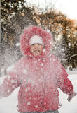 The little girl and snow. The girl threw snow and looking at the fluttering snowflakes Royalty Free Stock Photos