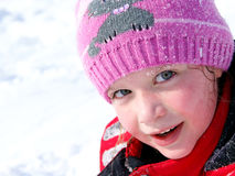 Little girl in the snow. Little smiling girl outdoors in the snow in winter clothing Stock Photo