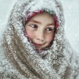 A little girl in a snow-covered shawl