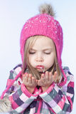 Little girl with snow in hands, blue background Stock Photography