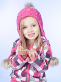Little girl with snow in hands, blue background Royalty Free Stock Images