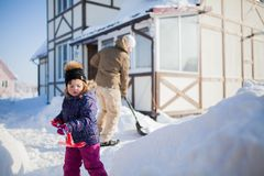 Little girl with a snow shovel. Royalty Free Stock Photography