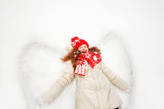 Little girl on a snow showing  angel figures. Royalty Free Stock Photo