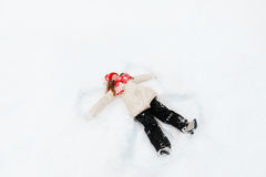 Little girl on a snow showing angel figures. Royalty Free Stock Photos