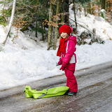 Little girl with snow sleds Stock Image