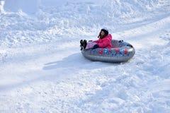Little girl snow tubing Stock Photos