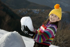 Little girl with snowball Stock Photos