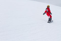 Little girl snowboarder riding down at ski slope  in French Alps Stock Images