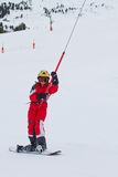 Little girl snowboarder rises up at ski-tow in French Alps Stock Images