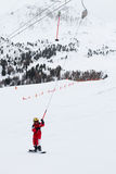 Little girl snowboarder rises up on ski-tow in French Alps Royalty Free Stock Images