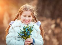 Little girl with a snowdrops Royalty Free Stock Images