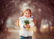 Little girl with a snowdrops Stock Photography