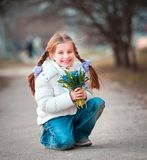 Little girl with a snowdrops Stock Photos