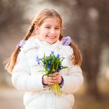 Little girl with a snowdrops Royalty Free Stock Image