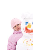 Little girl and snowman. Little girl looks out from behind snowman Royalty Free Stock Images