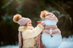 Little girl with snowman Royalty Free Stock Photos